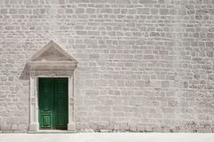 Marble framed door on limestone wall of church. White, stone built, church wall and green door framed with white marble royalty free stock photography
