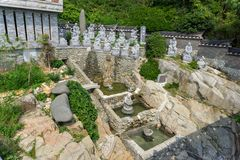 White stone carved statues of Chinese Buddha, priests and many animals on the artificial waterfall at Haedong Yonggungsa Temple. In Busan, South Korea royalty free stock photos