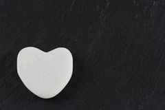 White stone heart on dark Stock Photography
