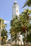 White stone lighthouse on a stony-sandy beach among green palms. Sri Lanka. Dondra. White stone lighthouse on a stony-sandy beach among green palms. The road to Stock Photography