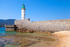 White stone lighthouse tower on the pier. Corsica. White stone lighthouse tower on the pier. Entrance to Propriano, Corsica island, France Royalty Free Stock Photography