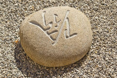 White stone lying in the gravel. Stone carved with Chinese characters lying in the gravel Stock Image