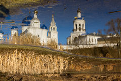 White-stone monastery with sky-blue domes, reflected in the edge of the last winter ice Stock Image