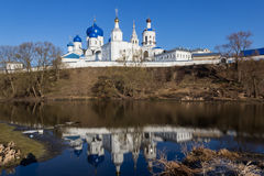 White-stone monastery with sky-blue domes, reflected in the edge of the last winter ice Royalty Free Stock Images