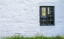 White, stone wall with a black window frame Royalty Free Stock Photography