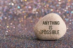 Anything is possible on stone. A white stone with words anything is possible and smile face on color glitter boke background stock photo