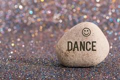 Dance on stone. A white stone with words dance and smile face on color glitter boke background stock photo