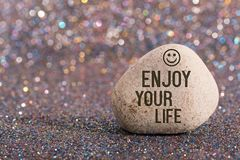 Enjoy your life on stone. A white stone with words enjoy your life and smile face on color glitter boke background royalty free stock photos