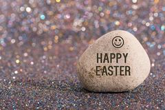Happy easter on stone. A white stone with words happy easter and smile face on color glitter boke background stock photo