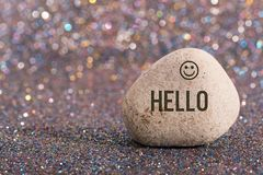 Hello on stone. A white stone with words hello and smile face on color glitter boke background stock photography