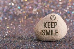 Keep smile on stone. A white stone with words keep smile and smile face on color glitter boke background Stock Image