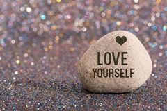 Love yourself on stone. A white stone with words love yourself and heart shape on color glitter boke background royalty free stock photo