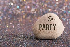 Party on stone. A white stone with words party and smile face on color glitter boke background royalty free stock photo