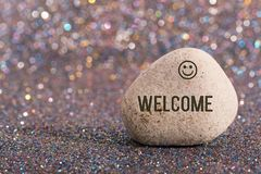 Welcome on stone. A white stone with words welcome and smile face on color glitter boke background stock images