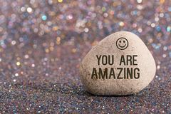 You are amazing on stone. A white stone with words you are amazing and smile face on color glitter boke background stock photos