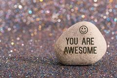 You are awesome on stone. A white stone with words you are awesome and smile face on color glitter boke background royalty free stock images