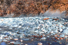 White stones in a mountain river on sunny day Stock Photography