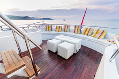 White stools and long seat on the yacht deck. Yacht deck setup with white furnitures preparing for a group party Stock Photos