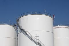 White storage tanks. Some large white storage tanks at an oil refinery Stock Photography