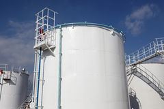 White storage tanks. At oil refinery, against the blue sky Royalty Free Stock Photography