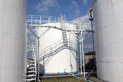 White storage tanks. At oil refinery, against the blue sky Royalty Free Stock Photos