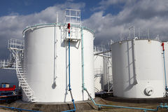 White storage tanks. At oil refinery, against the blue sky Stock Photo