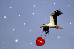 White stork with red heart. On a blue sky Royalty Free Stock Photos