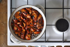 White stove with a pan of homemade apple compote. View from above Stock Photo