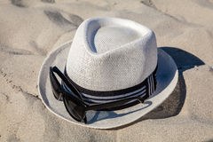 White Straw Fedora with Sunglasses on Beach Stock Image