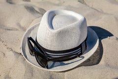 White Straw Fedora with Sunglasses on Beach. White straw fedora hat on sandy beach with black rimmed polarized sunglasses stock image