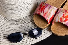 White Straw Hat, Beach Sandals and Sunglasses. White straw hat, beach sandals and a pair of blue shaded sunglasses stock photos