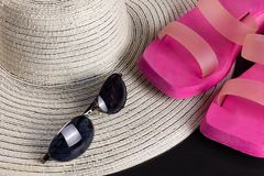 White Straw Hat, Beach Sandals and Sunglasses. White straw hat, purple beach sandals and a pair of blue shaded sunglasses royalty free stock photography
