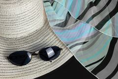 White Straw Hat, Foulard and Sunglasses. White straw hat, a black, blue and purple foulard and a pair of sunglasses royalty free stock photo