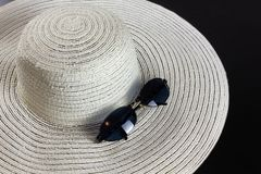 White Straw Hat and Sunglasses. White straw hat on a dark wooden background, with a pair of  blue shaded sunglasses stock photography