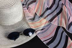 White Straw Hat, Foulard and Sunglasses. White straw hat, a pink and black foulard and a pair of blue shaded sunglasses royalty free stock photos