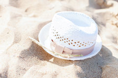 White straw hat lying in the sand on the beach Royalty Free Stock Photo
