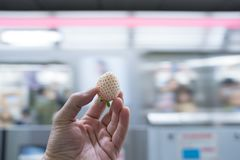 White strawberry type, but sweet and delicious was held in the hand with the subway / underground background. White strawberry type,  but sweet and delicious was royalty free stock image