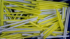White straws with blue lines and yellow straws with white lines in blue plastick container stock image