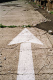Abandoned Street Arrow. White street arrow in a neglected abandoned street Royalty Free Stock Photos