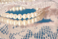 White string of pearls with pink lace. With reflection Stock Photography