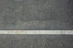 White strip of road markings on a new road, close-up photo. White strip of road markings on a new road Royalty Free Stock Photos