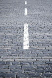 White strip on a stone blocks. White strip on the city square covered with a stone blocks Royalty Free Stock Image