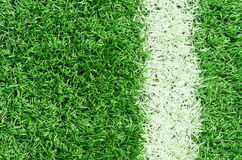 White stripe on artificial green grass of soccer field Stock Photos