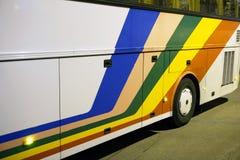 White stripe tour bus with tourists at night downtown the city.  Stock Photos
