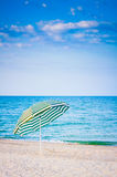 White striped umbrella on beach Royalty Free Stock Images