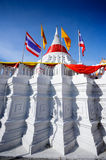 White stupa pagoda with red robe foreground Thailand flag blue sky background Royalty Free Stock Photo