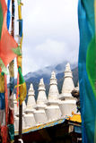White stupas and prayer flags. White stupas and colorful prayer flags in Tibet. China royalty free stock photography
