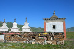 White stupas and prayer wheel buildings on Tibetan Plateau Royalty Free Stock Photography