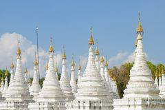 White stupas Sandarmuni Pagoda. Mandalay, Burma. White stupas Sandarmuni Pagoda on a sunny day. Mandalay, Burma stock photography