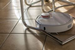 Modern robotic vacuum cleans in all corners stock photo